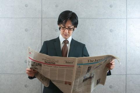 新聞を読んでいる男性